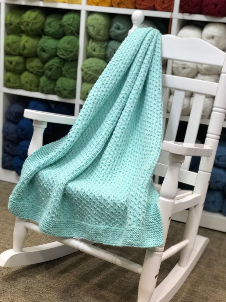 knitted baby throw in mint colored aran weight yarn.